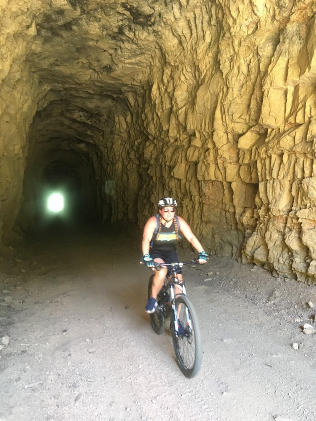 U.S. Army Spc. Jennifer Davenport, assigned to the Soldier Recovery Unit at Fort Carson, Colo., rides a mountain bike through a cave. Davenport began cycling while in the Army Recovery Care Program. (U.S. Army courtesy photo)