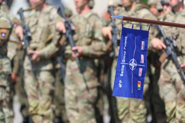The enhanced Forward Presence Battle Group Poland guidon is held in front of a formation of Soldiers during a change of command ceremony in Bemowo Piskie Training Area, Poland, July 17, 2020. After a 6-month rotation, 3rd Squadron, 2nd Cavalry Regiment was replaced by 2nd Squadron, 2nd Cavalry Regiment. (U.S. Army photo by Cpl. Justin W. Stafford)