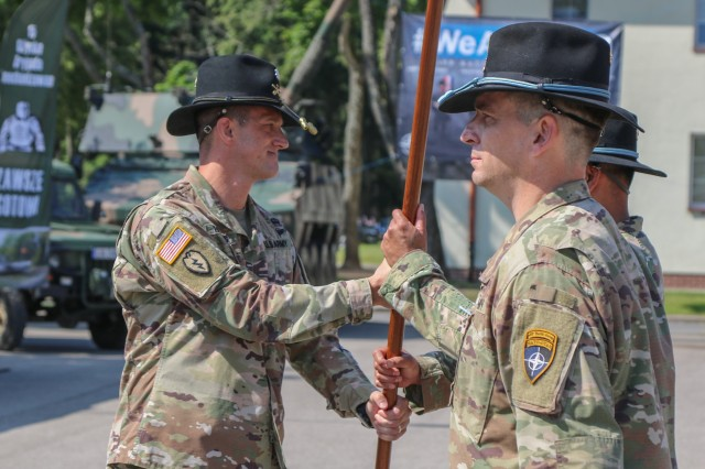 U.S. Army Lt. Col. Jeffery Higgins, the incoming Battle Group Poland commander, passes a guidon to Command Sgt. Maj. Keneti Pauulu, the incoming command sergeants major for the battle group, during a change of command ceremony in Bemowo Piskie Training Area, Poland, July 17, 2020. After a 6-month rotation, 3rd Squadron, 2nd Cavalry Regiment was replaced by 2nd Squadron, 2nd Cavalry Regiment. (U.S. Army photo by Cpl. Justin W. Stafford)
