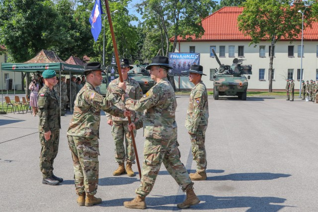 U.S. Army Command Sgt. Maj. Marcus Brister, assigned to 3rd Squadron, 2nd Cavalry Regiment, passes a guidon to Lt. Col. Andrew Gallo, the 3/2 CR and outgoing Battle Group Poland commander, during a change of command ceremony in Bemowo Piskie Training Area, Poland, July 17, 2020. After a 6-month rotation, 3rd Squadron, 2nd Cavalry Regiment was replaced by 2nd Squadron, 2nd Cavalry Regiment. (U.S. Army photo by Cpl. Justin W. Stafford)