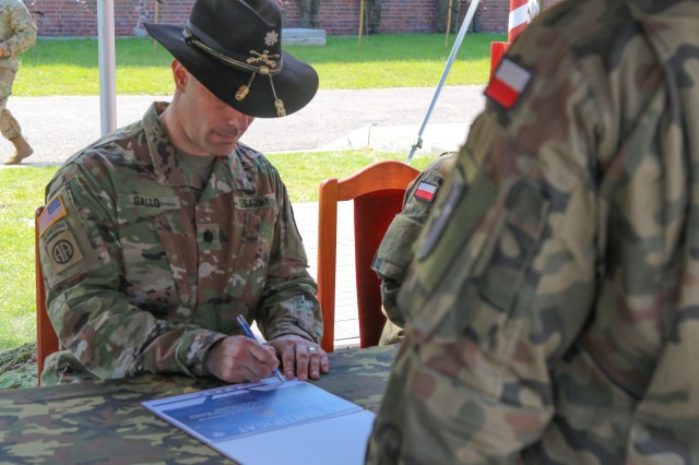 U.S. Army Lt. Col. Andrew Gallo, 3rd Squadron, 2nd Cavalry Regiment commander and outgoing Battle Group Poland commander, signs a transfer of authority during a change of command ceremony in Bemowo Piskie Training Area, Poland, July 17, 2020. After a 6-month rotation, 3rd Squadron, 2nd Cavalry Regiment was replaced by 2nd Squadron, 2nd Cavalry Regiment. (U.S. Army photo by Cpl. Justin W. Stafford)