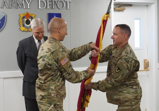 Col. Steven Dowgielewicz (left) grabs unit colors symbolically assuming command of Tooele Army Depot from Col. Todd Burnley (right).