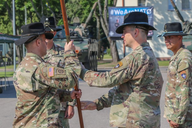 U.S. Army Command Sgt. Maj. Marcus Brister, assigned to 3rd Squadron, 2nd Cavalry Regiment, passes a guidon to Lt. Col. Andrew Gallo, the outgoing Battle Group Poland commander during a change of command ceremony in Bemowo Piskie Training Area, Poland, July 17, 2020. Gallo relinquished his command of the battle group to Lt. Col. Jeffery Higgins, assigned to 2nd Squadron, 2nd Cavalry Regiment. (U.S. Army photo by Cpl. Justin W. Stafford)