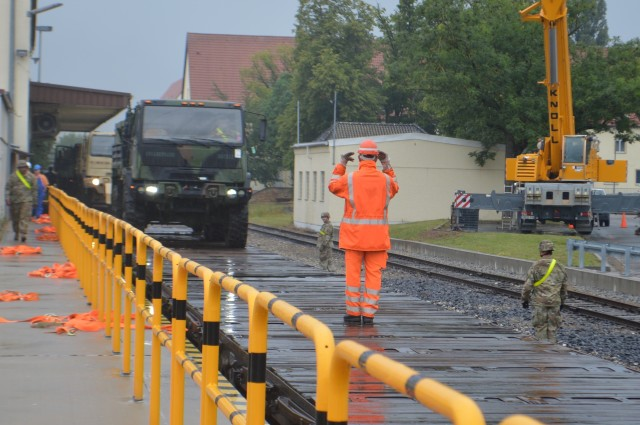 A Deutsches Bahn railroad employee guides a truck while it is offloaded from a train July 16, 2020, during the largest rail operation U.S. Army Garrison Ansbach, Germany, conducted in more than 10 years. The trucks and equipment belong to the 101st Combat Aviation Brigade, the incoming Regionally Allocated Force that will be stationed at Storck Barracks, Illesheim, for their nine-month rotation supporting Atlantic Resolve. The Katterbach Railhead provides U.S. Army in Europe an additional power projection platform capability to deploy arriving and departing brigade-size elements to meet strategic objectives.