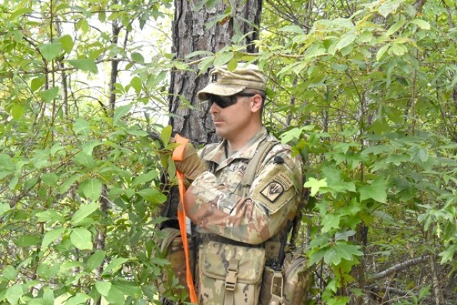 Capt. Aaron Scherffius, JRTC Operations Group Task Force 5, uses a compass to determine the angle for felling a tree to build an abatis.