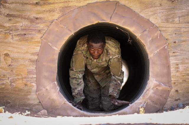 FORT BLISS, Texas - Pfc. Seyi Hunsa, a cannon crewmember assigned to 4th Battalion, 27th Field Artillery Regiment, 2nd Armored Brigade Combat Team, 1st Armored Division and whose hometown is Burgaw, North Carolina, exits a tunnel and races to complete the final portion of the Fort Bliss obstacle course during the 1AD Best Warrior Competition, May 15. The obstacle course included climbing ropes, scaling barriers and events which tested the Soldier's ability to maintain composure and confidence at height. The competition pitted 10 competitors representing each of 1AD's brigades against each other through a series of physical and mental tasks, concluding with an interview conducted by the division operations sergeant major, in order to determine the division's Soldier and Noncommissioned Officer of the year. This year's competition was won by Staff Sgt. James Ferrone, a cavalry scout assigned to Troop B,  2nd Squadron, 13th Cavalry Regiment, 3rd Armored Brigade Combat Team and native of Naperville, Illinois, and Spc. Gage Paraschos, a cavalry scout assigned to Troop C, 2-13 CAV whose hometown is Mount Bethel, Pennsylvania, after they displayed their excellence in skills, knowledge and physical fitness. (U.S. Army photo by Pfc. Matthew Marcellus)