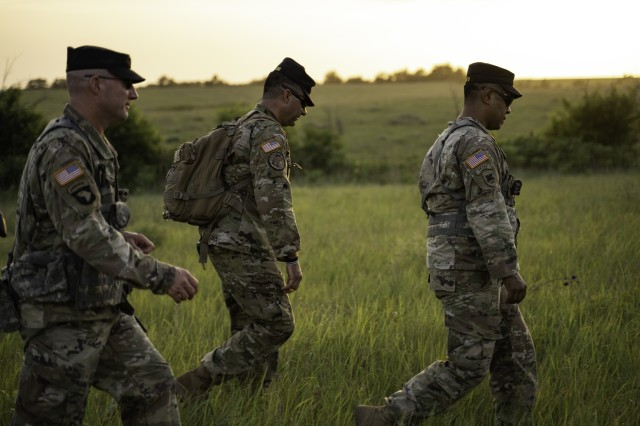 Maj. Eric Deeds, company commander of Officer Candidate School, 1st Battalion, 235th Regiment, and instructors Capt. Adam Taylor and Sgt. 1st Class Dominic Cantu walk back to the starting point of an exercise at the conclusion of the final situational training exercise of the day for class 64. Class 64 conducted training at the Kansas National Guard Range Training Complex, June 27, 2020. Cadets trained in preparation for the final phase of their journey to become officers. (Photo by Capt. Lauren Orr, 105th Mobile Public Affairs Detachment.)