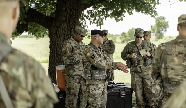 Maj. Eric Deeds, commander of the Officer Candidate School, 1st Battalion, 235th Regiment, gives valuable advice on potential improvements during the candidates' operations order brief. Class 64 conducted training at the Kansas National Guard Range Training Complex in Salina, Kansas, June 27-28, in preparation for the final phase of their journey to become officers. (Photo by Capt. Lauren Orr, 105th Mobile Public Affairs Detachment.)