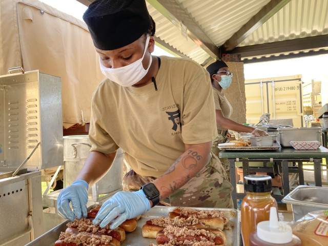 Specialist Keilah Jones, a culinary specialist assigned to 1st Battalion, 187th Infantry Regiment, 3rd Brigade Combat Team, 101st Airborne Division (Air Assault), prepares a pulled pork gourmet hot dog, named the Back Yard Pit Dog, for the Hot Dog Cook-off July 15 between battalions outside the Rak Café using field feeding equipment. The contest also provided a training opportunity for the Soldier-chefs. (Stephanie Ingersoll, Fort Campbell Courier)