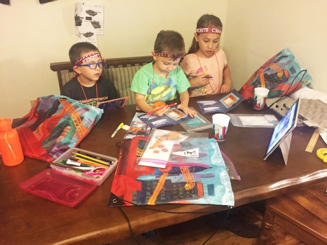 Norman Malinowski (left), 6, his brother, Edmond (center), 4, and sister, Beatrix, 8, work on crafts while watching the Fort Polk Main Post Chapel hybrid vacation bible school lesson online.