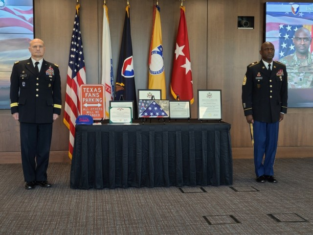Gen. Edward Daly, left, commanding general of Army Materiel Command, and Command Sgt. Maj. Gene Canada, right, USASAC's former command sergeant major, listen to a Legion of Merit awards citation at a retirement ceremony honoring Canada's 33 years of military service to our nation. Canada served as the third command sergeant major in USASAC's 55-year history, and earlier in the day turned over responsibility for the command to incoming Command Sgt. Maj. Sean Rice. (Photo by Terri Stover, USASAC Public Affairs)