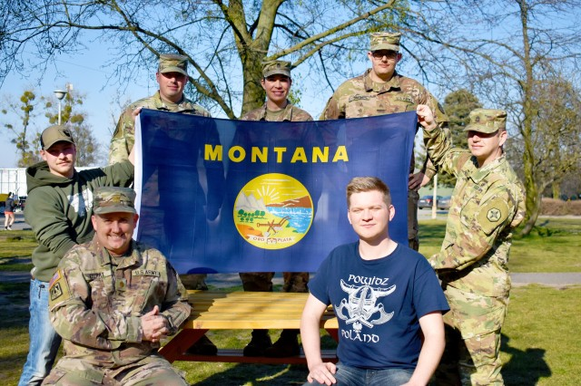"""Clockwise from left, seated: Maj. Colin Curry, Spc. Dylan Roselles, Maj. Brian Casey, 1st Sgt. Alicia Roethler, Sgt. Colton Smith, Sgt. 1st Class John Proulx, and Pfc. Koleton Grimes, all Soldiers from the 652nd Regional Support Group out of Helena, Montana, pose with the Montana state flag April 6, 2020 on """"406"""" day in Powidz, Poland. The Montana Soldiers with the 652nd RSG are wrapping up a nearly year-long deployment to Poland by quarantining at North Fort Hood, Texas. (U.S. Army Reserve photo by Maj. Olha Vandergriff, 652nd Regional Support Group)"""