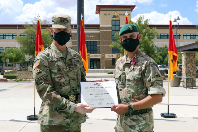 Fort Bliss, Texas - Maj. Gen. Patrick Matlock, the commanding general of 1st Armored Division and Fort Bliss (left), awards the Legion of Merit to British Army Brigadier Leigh Tingey, a native of Cambridge, England, the outgoing deputy commanding general-maneuver of 1AD (right), during a farewell retreat ceremony held in Tingey's honor at Fort Bliss, Texas, July 23. (U.S. Army photo by Jean S. Han)