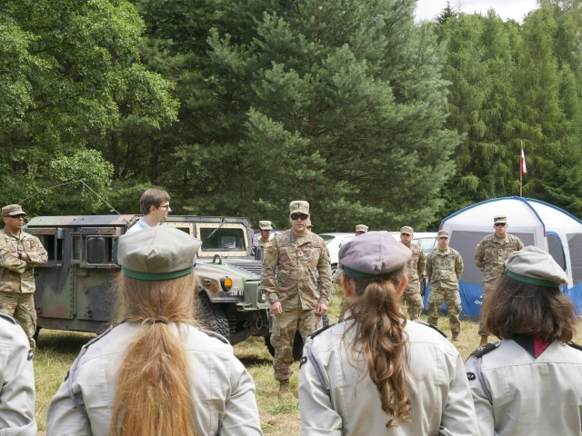 U.S. Army 1st Lt. Eduardo Santiago, detachment commander for the 266th Ordinance Company, a Reserve unit out of Puerto Rico, speaks with Polish scouts about his unit's mission in support of Atlantic Resolve at Camp Watra near Osieczow, Poland, July 17, 2020.  U.S. Army Soldiers from the Alaska National Guard's 297th Regional Support Group and U.S. Army Reserve's Bravo Company, 418th Civil Affairs Battalion, out of Missouri, joined the 266th OD to learn about the history and values of the Polish scouting organization while sharing their units' missions and high-mobility multipurpose wheeled and medium tactical vehicles that are assigned to nearby FOS Świętoszów.  (U.S. Army National Guard photo by Sgt. 1st Class Dayton Will)