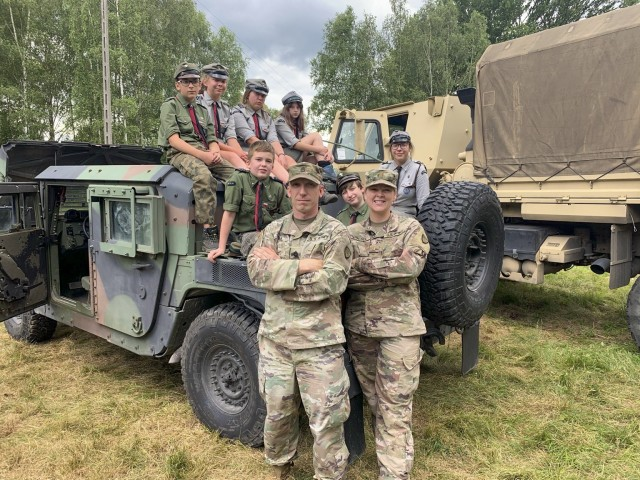 U.S. Army Sgt. 1st Class Dayton Will, left, Forward Operating Site Świętoszów deputy mayor and 2nd Lt. Balinda Dresel, FOS Świętoszów mayor, both with the Alaska National Guard's 297th Regional Support Group, pose for a picture with Polish scouts at Camp Watra near Osieczow, Poland, July 17, 2020.  The Alaska Guardsmen and Reservist with the 266th Ordinance Company, out of Puerto Rico, and Bravo Company, 418th Civil Affairs Battalion, out of Missouri, learned about the history and values of the Polish scouting organization while sharing their units' missions and high-mobility multipurpose wheeled and medium tactical vehicles that are assigned to nearby FOS Świętoszów.