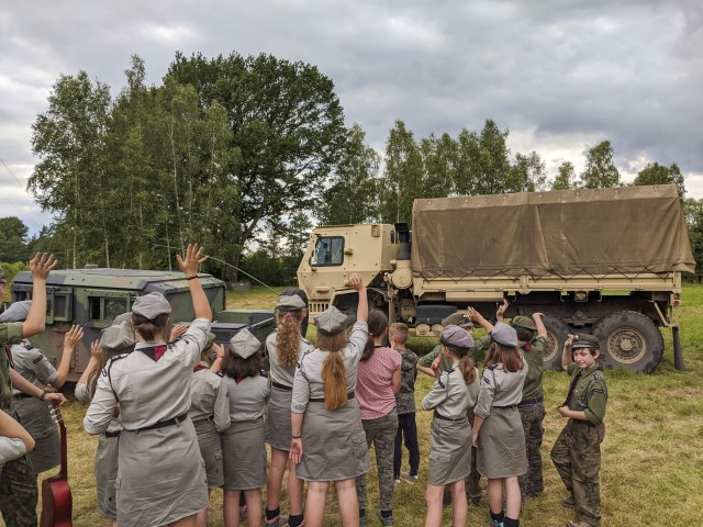 Polish scouts wave farewell to U.S. Soldiers in high-mobility multipurpose wheeled and medium tactical vehicles belonging to the U.S. Army Reserve's 266th Ordinance Company, out of Puerto Rico, at Camp Watra near Osieczow, Poland, July 17, 2020.  U.S. Army Soldiers from the Alaska National Guard's 297th Regional Support Group and U.S. Army Reserve's Bravo Company, 418th Civil Affairs Battalion, out of Missouri, joined the 266th OD to learn about the history and values of the Polish scouting organization while sharing their unit's missions in support of Operation Atlantic Resolve.