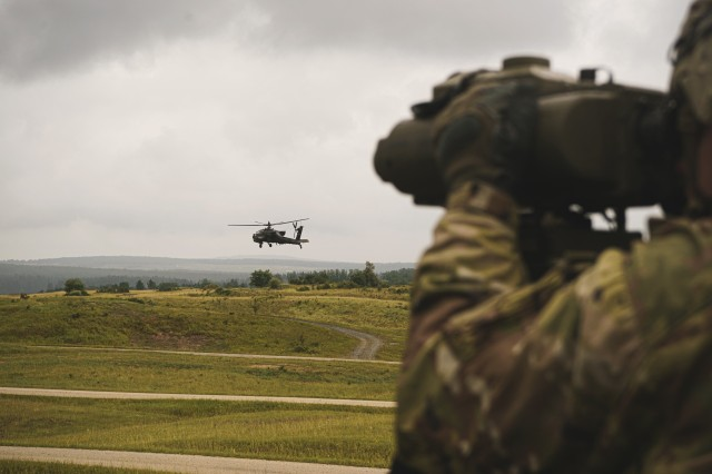 U.S. Soldier, assigned to the 1st Squadron, 2d Cavalry Regiment, watches an AH-64 Apache helicopter with the 12th Combat Aviation Brigade during a gunnery training in Grafenwoehr Training Area, Germany, July 16, 2020. The gunnery training concluded with the squadron's table VIII and IX live-fire certifications. (U.S. Army photo by Sgt. LaShic Patterson)