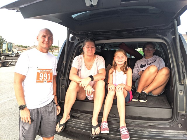 From left to right, U.S. Army Capt. Joshua Barlow, left, 1st Infantry Division Headquarters and Headquarters Battalion, , his wife Carole, and daughters Isabella and Laura, await the start of the 10-5-2 race at Fort Riley, Kansas, July 25, 2020.
