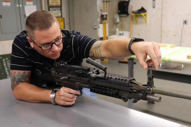 David Blaylock, Simulation & Test Range Division chief at Rock Island Arsenal – Joint Manufacturing Technology Center, uses an M249 sight adjustment tool on the front sights of an M240 machine gun. (Photo by Randl Besse, Deputy Project Manager, Rock Island Arsenal, Joint Manufacturing Technology Center)