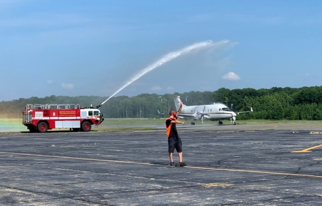 "Jon Gregory pilots the CARA C-12J2 (the only one in the Army aircraft inventory) down the Phillips Airfield runway under the aviator's traditional ""hose down"" welcome during his last flight."