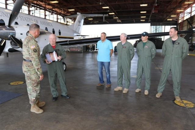 Standing next to their C-12J2 aircraft, Jon Gregory, with CARA teammates, receives the Army Risk Management Award, on behalf of the Army Aviation Safety Center, from Brig. Gen. William King in 2017.