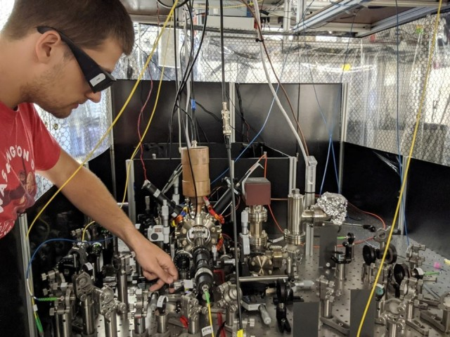 John Hannegan, a graduate student and research scientist at the University of Maryland, adjusts photon collection optics in preparation for linking the trapped ion lab with another quantum lab.