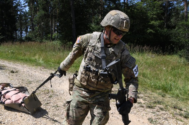U.S. Army Staff Sgt. William McLain, explosive ordnance disposal specialist, 18th Sustainment Brigade, pulls a Skedco during the U.S. Army Europe European Best Warrior Competition at U.S. Army Garrison Hohenfels Training Area, Germany, July 29, 2020. The competition is an annual event with competitors assigned to United States Army Europe and United States Army Africa. Officers, noncommissioned officers and junior enlisted Soldiers compete in separate categories and are evaluated on general military, physical fitness and common military tasks. Winners in the NCO and junior enlisted categories will advance to represent U.S. Army Europe at the Army Best Warrior Competition at For Lee, Virginia. For more information about the competition, visit https://www.eur.army.mil/EBWC/. (U.S. Army photo by Spc. Austin Riel)