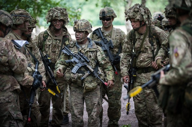 "Staff Sgt. Nilberto Navarro, center, a squad leader in the 51st Transportation Company, briefs his Soldiers and performs pre-combat checks prior to the start of a training patrol July 29, 2015, in Sennelager, Germany. As part of the ""This is My Squad"" initiative, the Army is developing a new mobile app to help leaders better connect with squad members and manage everyday tasks."
