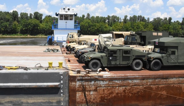 Vehicles belonging to the 2nd Brigade Combat Team, 101st Airborne Division, from Fort Campbell, Ky., prepare to off-load from a barge at the Central Louisiana Regional Port in Alexandria, La., Aug. 3.