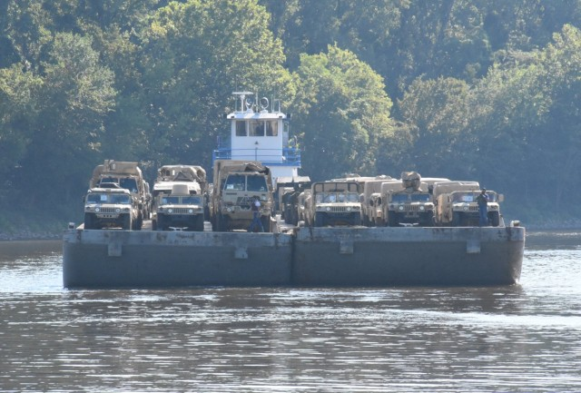 A barge pushing a deck carrying vehicles assigned to the 2nd Brigade Combat Team, 10th Airborne Division (Air Assault), moves into place at the Central Louisiana Regional Port in Alexandria, La. Aug. 3. The vehicles were off-loaded and then convoyed 40 miles to the Joint Readiness Training Center and Fort Polk for the unit's Rotation 20-09.