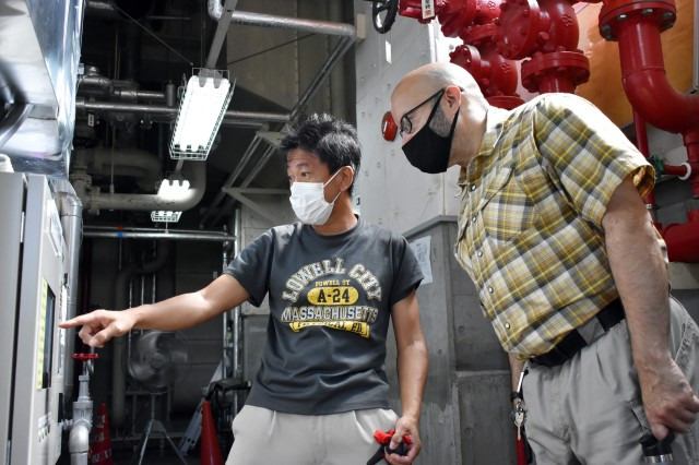 Makoto Akabame, left, a mechanical system inspector for the Directorate of Public Works, U.S. Army Garrison Japan, and David Crespo, chief of the directorate's mechanical and sanitation branch, look at a monitor while overseeing an air conditioning repair in Building 1050 at Camp Zama, Japan, Aug. 6.