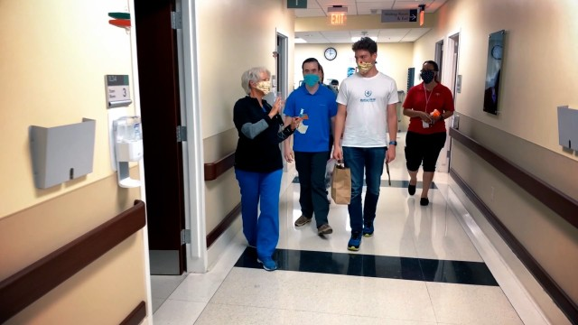 Winn Army Community Hospital nurse, Pam Risner, (Left) accompanied by Winn FRSA Richele Martinez (Right), escort Chris Larson and Mathiew Tackitt through Winn ACH as Tackitt and Larson deliver Facemask and mask extenders to healthcare providers on Fort Stewart.   (Photo by Zach Rehnstrom)
