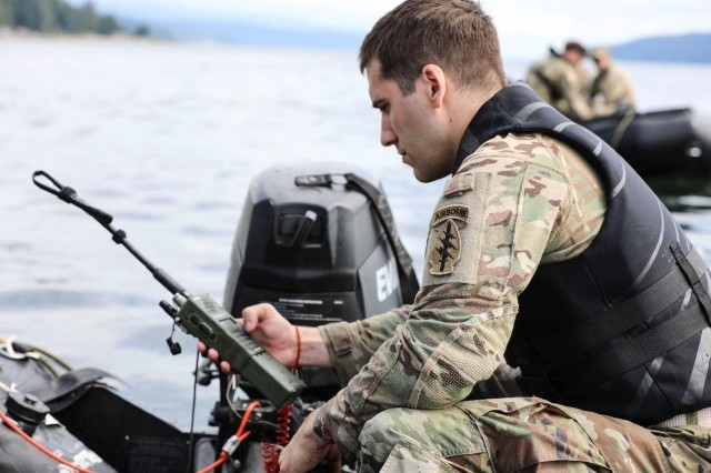 A U.S. Army Green Beret with 1st Special Forces Group synchronizes a radio during Joint Precision Airdrop System (JPADS) and military freefall (MFF) exercise on July 24, 2020, in Shelton, Washington. Capabilities like the Dismounted Distributed Tactical Beamforming System and the Squad Area Network provide dismounted Soldiers with reach-back to the platoon level and allow for more effective operations by increasing situational awareness and coordination within squads.