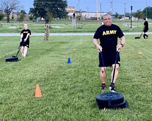 BACH Soldiers Capt. Erin Baughman, an optometrist, and Command Sgt. Maj. Daniel Santiago, senior enlisted advisor, each pull a 90-pound sled during the drag portion of the Sprint-Drag-Carry event of the new Army Combat Fitness Test. The event relates to Soldier tasks performed when reacting quickly to direct or indirect fire, extracting a casualty from a vehicle and getting them to safety, and carrying ammunition to a fighting position or vehicle. The AFCT replaces the Army Physical Fitness Test as the test of record Oct. 1. U.S. Army photo by Sgt. 1st Class Jamie Hendzel.