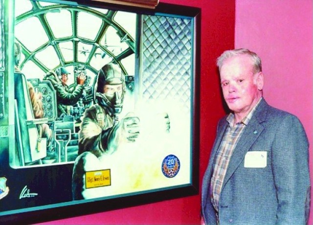 Red Erwin stands with a painting depicting his act of heroism in the B-29 bomber, City of Los Angeles, on that fateful day.