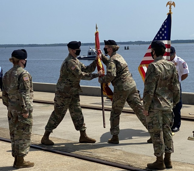 Col. William Arnold, the new 596th Transportation Brigade commander, returns the guidon to CSM Kerstin Montoya after receiving it from Brig. Gen. Heidi J. Hoyle, SDDC commanding general, during a change of command ceremony August 11, 2020 at the Military Ocean Terminal Sunny Point in Southport, North Carolina. (U.S. Army photo by Augustin Gonzalez)