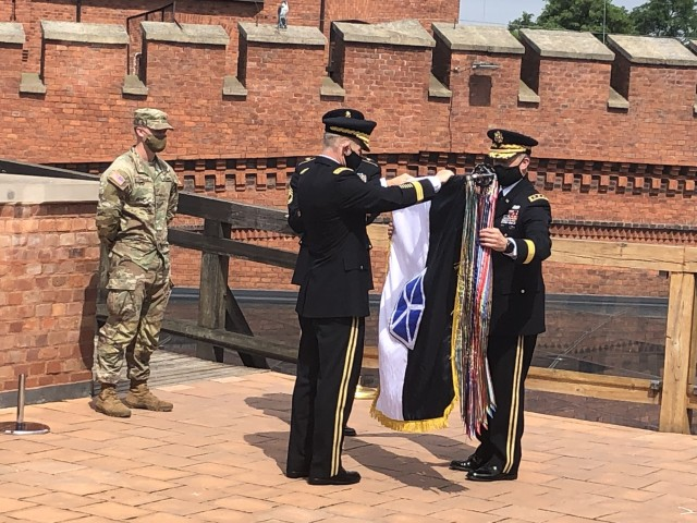 Lt. Gen Christopher Cavoli observes U.S. Army Chief of Staff Gen. James C. McConville and Lt. Gen. John Kolasheskis, V Corps commanding general, officially unfurl the V Corps flag during a ceremony in Krakow, Poland, Aug. 4. The primary mission of V Corps Headquarters (Forward) will be conducting operational planning, mission command oversight of rotational forces in Europe and will provide additional support to allies and partners in the region.