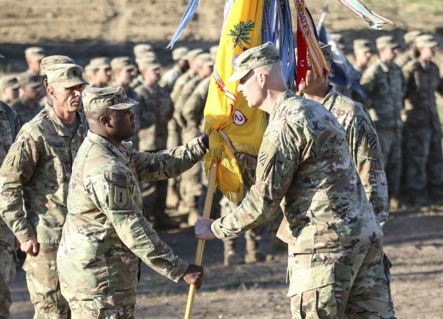 Col. Patrick S. O'Neal, commander of 2nd Armored Brigade Combat Team, 3rd Infantry Division, passes the 2nd Battalion, 69th Armored Regiment colors to Lt. Col. George Bolton, signifying the transfer of command during the battalion's change of command ceremony at Camp Mustang, Glebokie, Drawsko Pormoskie Training Area, June 1, 2020. (U.S. Army photo by Staff Sgt. Brian K. Ragin Jr.)