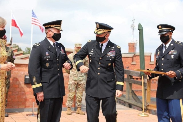 U.S. Army Chief of Staff Gen. James C. McConville and V Corps commanding general Lt. Gen. John Kolasheskis forgo shaking hands and follow COVID 19 safety procedures by touching elbows during his promotion and the official unfurling the V Corps flag ceremony in Krakow, Poland, Aug. 4. The primary mission of V Corps Headquarters (Forward) will be conducting operational planning, mission command oversight of rotational forces in Europe and will provide additional support to allies and partners in the region.