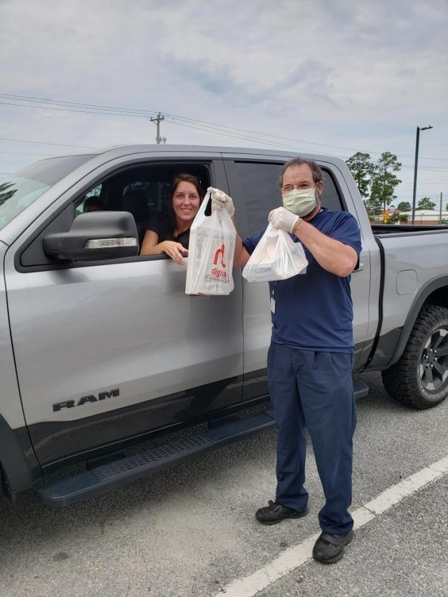 Andrew Sohlstrom, a library technician at George P. Hays Library, delivers a curbside order to Crystal Constable, a military Family member, Aug. 11 at the library parking lot on Fort Stewart. (Courtesy photo)