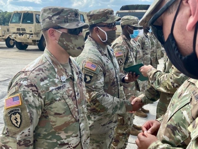 Lt. Col. Jeffery Fuller and Command Sgt. Maj. Antonio Morris, commander and senior enlisted leader of 1-41 FA, 1ABCT, 3rd ID, award the Expert Gunner badge to Staff Sgts. Johnpaul Taylor and Willy Zapata Aug. 7 on Fort Stewart. (U.S. Army photo by Maj. Jeremy Blascak)