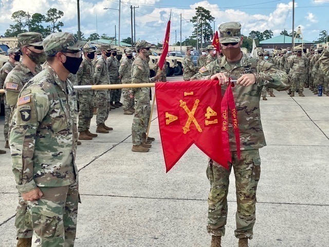 Lt. Col. Jeffery Fuller, commander of 1-41 FA, 1ABCT, 3rd ID, places the Top Gun and Top Fire Direction Center streamers on Alpha battery's guidon Aug. 7 on Fort Stewart. Soldiers assigned to 1-41 competed for the Top Gun and Top Field Direction Center awards and the Expert Gunner Badge. (U.S. Army photo by Maj. Jeremy Blascak)