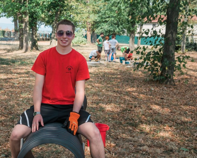 WIESBADEN, Germany - Tyler Houk sits on a section of the dog tunnel while volunteer scouts build the ramp component of the project at the dog park on Clay Kaserne August 12, 2020.