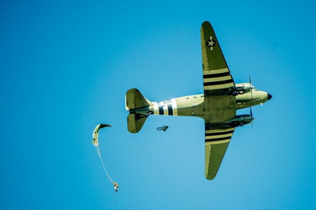 FORT BENNING, Ga. –  A World War II-vintage C-47 transport plane makes an airdrop over Fort Benning's Fryar Drop Zone Aug. 16, 2019, in observance on National Airborne Day. Making the jump were historical re-enactors in World War II paratrooper uniforms. Fort Benning is birthplace of the U.S. Army Airborne, and home to the U.S. Army Airborne School, which trains paratroopers for the Army and other services. President George W. Bush established National Airborne Day in 2001 to commemorate a series of test parachute jumps that were completed Aug. 16, 1940 by the U.S. Army Parachute Test Platoon, leading to formation of the Army's Airborne units that fought in World War II. It is observed every Aug. 16.  (U.S. Army photo by Patrick A. Albright, Maneuver Center of Excellence and Fort Benning Public Affairs Office)