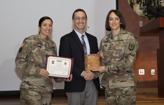 Col. Deydre Teyhen and Command Sgt. Maj. Natasha Santiago recognize and thank Dr. John Mascola, National Institute of Allergy and Infectious Disease, at WRAIR's 2019 event marking World AIDS Day on November 26, 2019