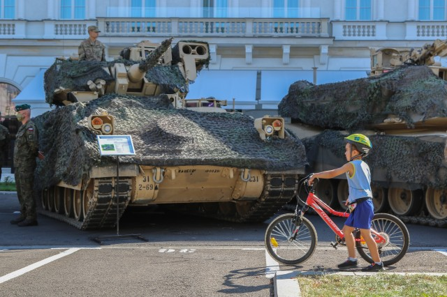 A boy pushes his bicycle in front of tanks, which are part of a static display, during events commemorating the 100th anniversary of the Battle of Warsaw and Armed Forces Day in Warsaw, Poland, Aug. 15, 2020. U.S. participation in the ceremony was to honor Poland's past, as well as show commitment to the future with Poland as allies. (U.S. Army photo by Cpl. Justin W. Stafford)