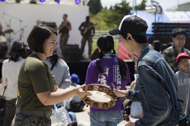 A member of the local community hits a tambourine during the Fuji Flightline Festival May 4 on Combined Arms Training Center Camp Fuji, Japan. The Flightline Festival is an annual event designed to bring members of the local community on base to build relationships, friendships and showcase the Marines' day-to-day operations. The Flightline Festival featured live band performances by local bands and the III Marine Expeditionary Force band, static displays and various food vendors.