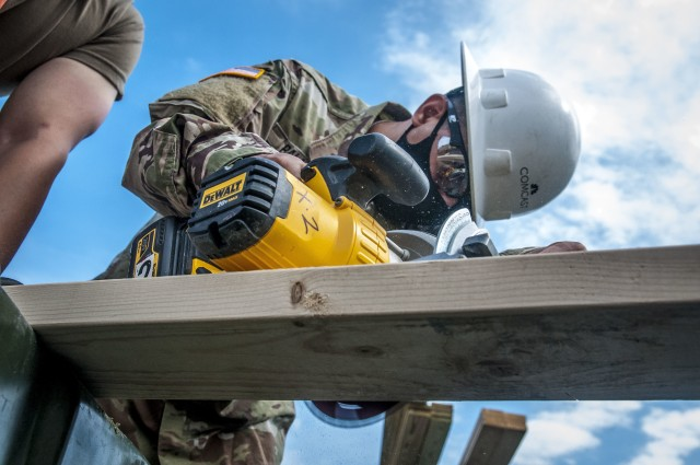 TAUNTON, Mass. – A Soldier assigned to the 338th Engineer Company cuts a plank of wood in preparation to construct a gazebo at the Army Reserve Center, here, Aug. 13, 2020. This construction project will help provide a shaded area for Soldiers to take breaks while working in the motor pool.