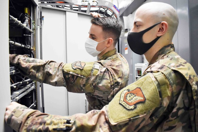 Air Force Staff Sgt. Christopher Watson, left, and Senior Airman Brandon Boiles, assigned to 374th Communications Squadron's Operating Location C, work in Building 771 at Camp Zama, Japan, July 24.