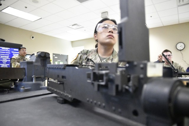 Pfc. Jane Seo, Bravo Company, 832nd Ordnance Battalion, looks up at the instructional TV screen during a demonstration by her instructor during 94T Short Range Air Defense System Repairer Course training Aug. 12.